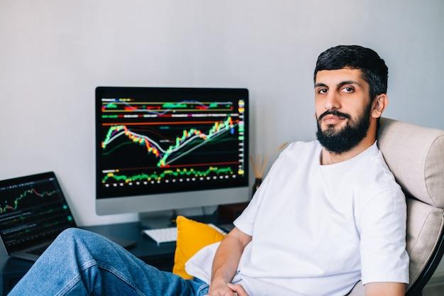 Porträt des kaukasischen geschäftsmannes, der online handelt, computer auf börsenhandel verwendend.