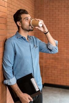 Porträt des kaukasischen geschäftsmannes des nahen ostens, der kaffee von der einwegkaffeetasse und der zwischenablage im besprechungsraum nach der mittagspause trinkt.
