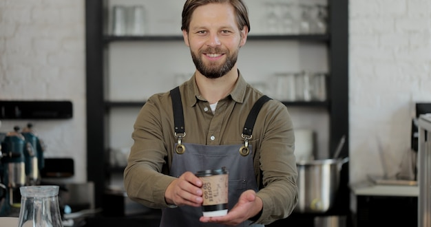 Porträt des kaukasischen hübschen männlichen barista und der handschuhe, die der kamera tasse kaffee geben und lächeln. barista, die im café kaffee zum mitnehmen übergibt.