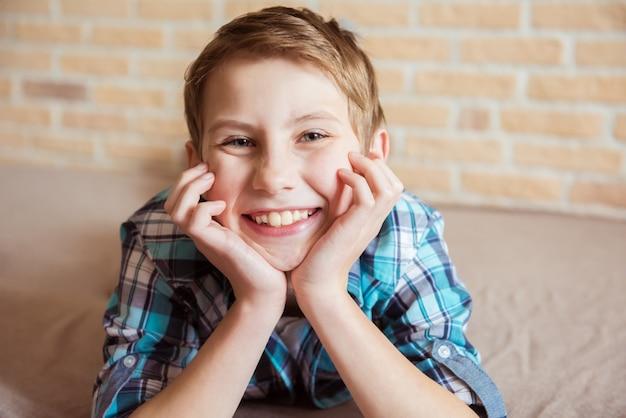 Porträt des kaukasischen jugendlich jungen mit kinn in den händen, die betrachter betrachten und lächeln