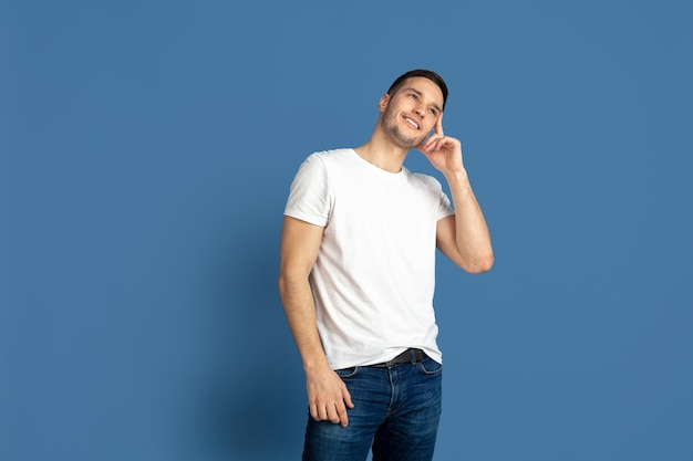 Porträt des kaukasischen jungen mannes auf blauer wand