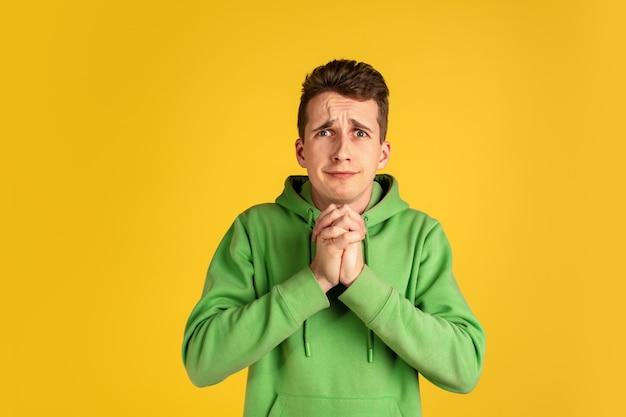 Porträt des kaukasischen jungen mannes auf gelber wand. schönes männliches modell im grünen outfit gestikulierend. konzept der menschlichen emotionen, gesichtsausdruck, verkauf, anzeige, jugend. copyspace.
