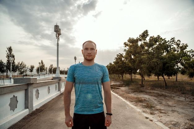 Porträt des kaukasischen kerls in einem blauen t-shirt und in schwarzen kurzen hosen, die auf der asphaltbahn während des sonnenuntergangs ausbilden und laufen