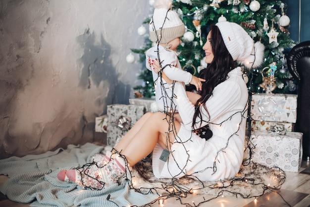 Porträt des kaukasischen kleinen babys haben viel spaß mit seiner mutter in der nähe des weihnachtsbaumes