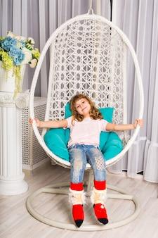 Porträt des kaukasischen lächelnden lachenden babys, das im stuhl sitzt und direkt in die kamera schaut.