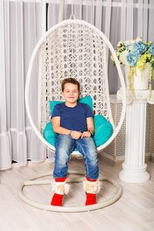 Porträt des kaukasischen lächelnden lachenden babys, das im stuhl sitzt und direkt schaut