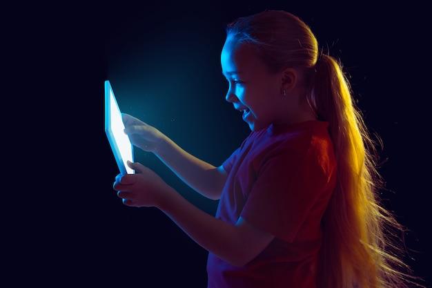 Porträt des kaukasischen mädchens lokalisiert auf dunkelheit im neonlicht