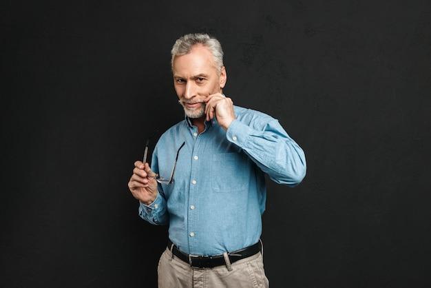 Porträt des kaukasischen mannes 60s mit grauem haar und bart, der brille hält, während er seinen grauen schnurrbart berührt, lokalisiert über schwarzer wand