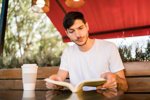Porträt des kaukasischen mannes, der freizeit genießt und ein buch liest, während draußen im café gesessen wird. lifestyle-konzept.