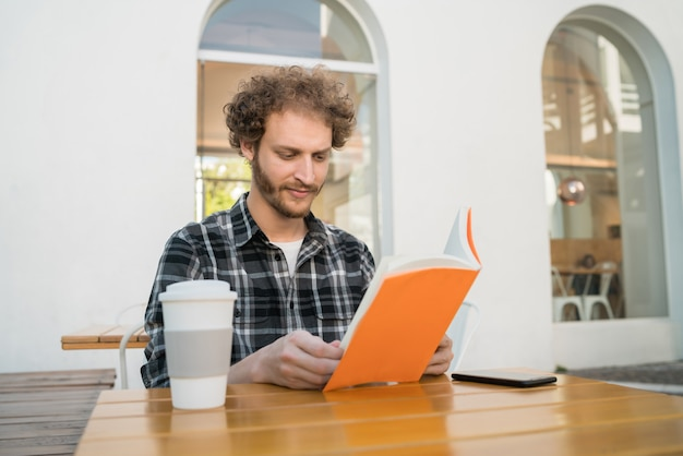 Porträt des kaukasischen mannes, der freizeit genießt und ein buch liest, während draußen im coffeeshop sitzt.