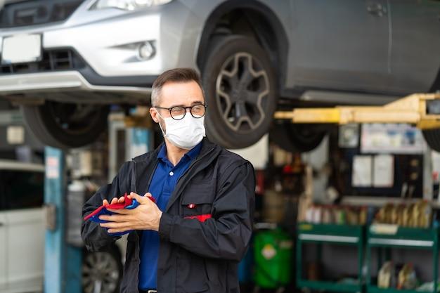 Porträt des kaukasischen mannes, der hände mit stoff reinigt und medizinisches gesichtsmaskenschutz-coronavirus trägt. fachmechaniker, der in autowerkstatt arbeitet.