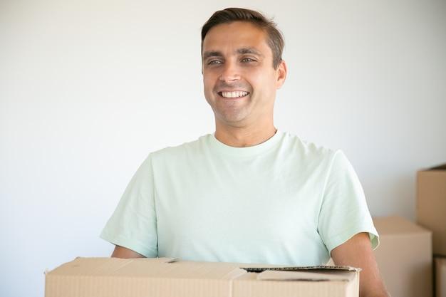 Porträt des kaukasischen mannes, der karton trägt und lächelt