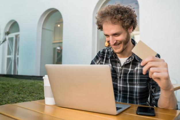 Porträt des kaukasischen mannes, der kreditkarte hält und laptop verwendet, um online in einem café einzukaufen