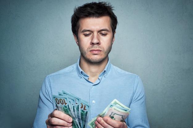 Porträt des kaukasischen mannes im hemd, das geld auf einem grauen wandhintergrund zählt. geschäfts- und finanzkonzept