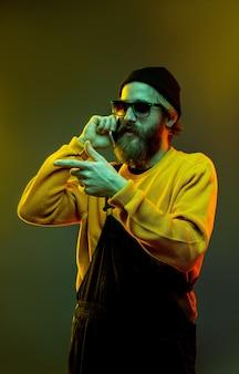 Porträt des kaukasischen mannes lokalisiert auf gradientenstudiohintergrund im neonlicht