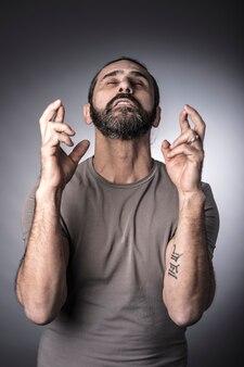 Porträt des kaukasischen mannüberfahrtfingers