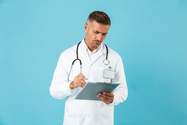 Porträt des kaukasischen medizinischen arztes mit stethoskop, das gesundheitskarte hält, lokalisiert über blauer wand