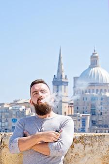 Porträt des kaukasischen mittlererwachsener mannes, der elektronische zigarette raucht,