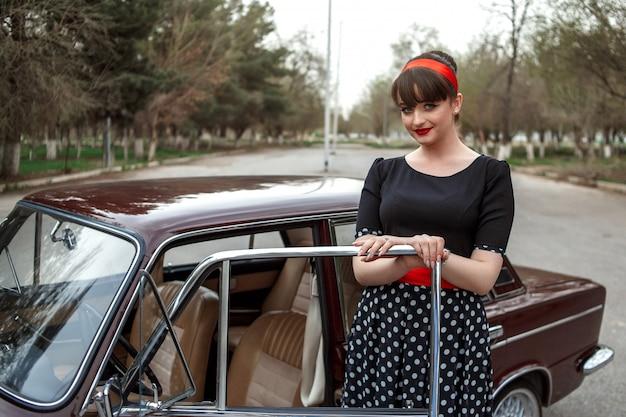 Porträt des kaukasischen schönen jungen mädchens im schwarzen weinlesekleid, das in einem retro- auto sitzt