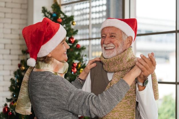 Porträt des kaukasischen senioren haben einen romantischen moment, der zusammen mit seiner frau zu hause auf dem weihnachts- und neujahrsfest tanzt. weihnachts- und neujahrsfeier-liebhaber-paar-aktivität.