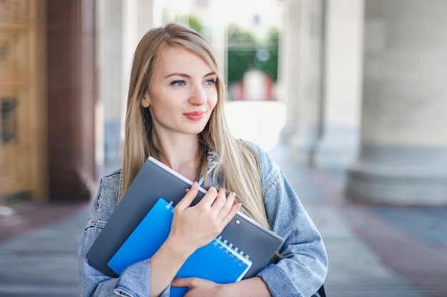 Porträt des kaukasischen studentenmädchens, das ordner, notizbuch-heft in den händen hält und nach rechts schaut, kopienraum