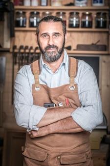 Porträt des kaukasischen tischlers in der werkstatt