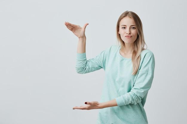 Porträt des kaukasischen weiblichen modells mit blonden haaren, die ihre lippen schmollen und größe der schachtel mit gegenwart demonstrieren, aktiv gestikulierend. körpersprache und gesichtsausdruck