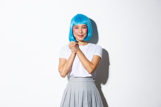 Porträt des kawaii asiatischen mädchens, das dankbar und amüsiert aussieht, hände zusammen fasst und lächelnd an der kamera erfreut, in der blauen perücke und im schulmädchenkostüm für halloween-party stehend.