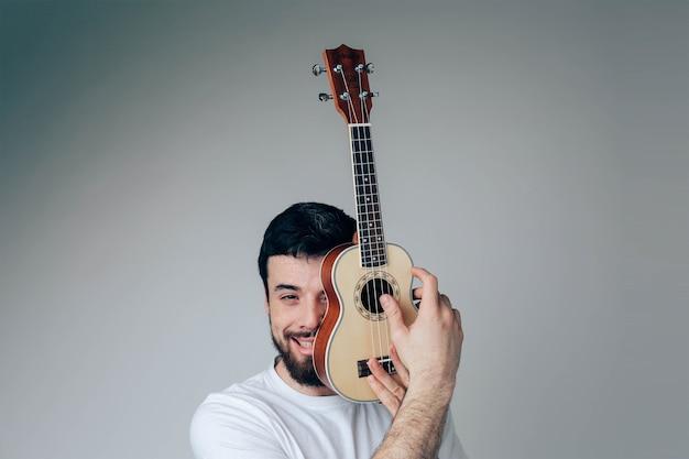 Porträt des kerlabdeckungsgesichtsteils mit kleiner ukulele