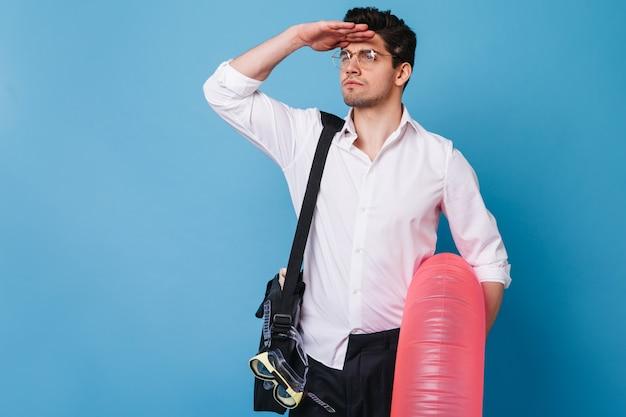 Porträt des kerls, der in die ferne auf blauem raum schaut. mann im weißen hemd und in den gläsern, die aufblasbaren kreis halten.