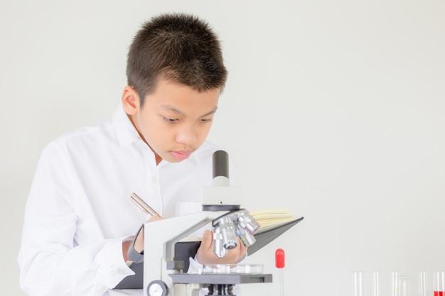 Porträt des kinderjungen, der mikroskop in der wissenschaftsstunde am labor verwendet und die ergebnisse notiert