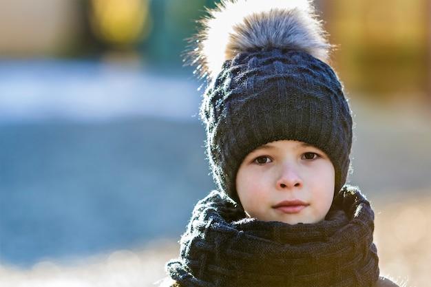 Porträt des kinderjungen in der mütze und im schal draußen im sonnigen wintertag