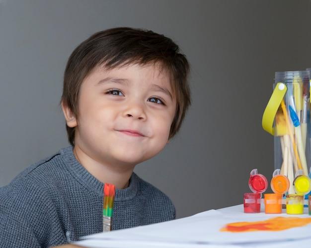 Porträt des kinderjungen spaßmalerei-wasserfarbe auf papier habend