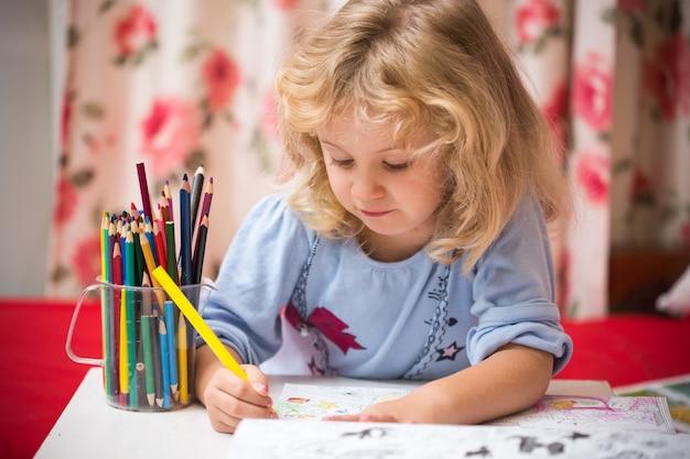 Porträt des kindermädchens, das mit bunten bleistiften zeichnet