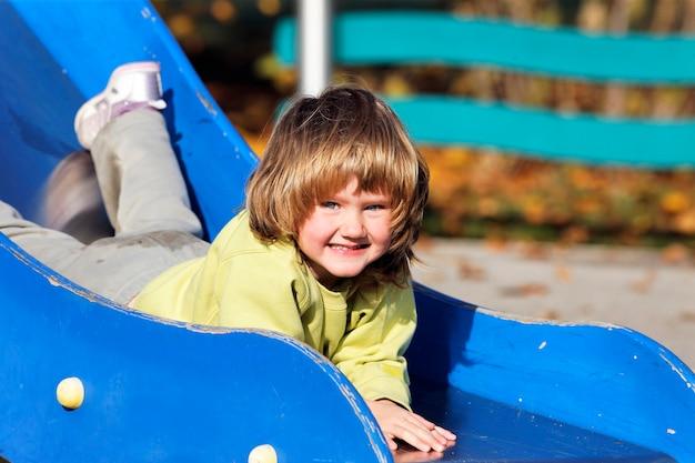 Porträt des kindes, das auf buntem spielplatz spielt