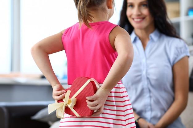 Porträt des kindes, das die herzförmige geschenkbox hinter dem rücken hält. freundliche und liebevolle beziehung zwischen tochter und mutter. konzept für kindheit und elternschaft