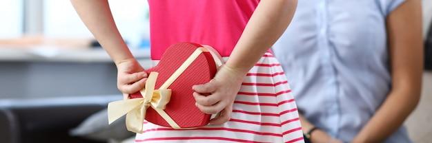 Porträt des kindes, das die herzförmige geschenkbox hinter dem rücken hält. freundliche und liebevolle beziehung zwischen tochter und mutter.