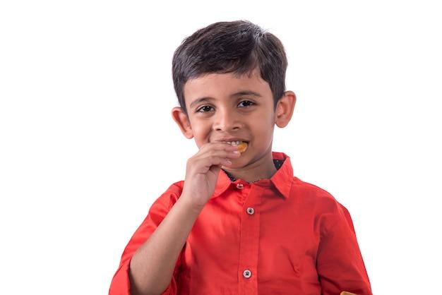 Porträt des kindes, das einen keks auf weiß isst