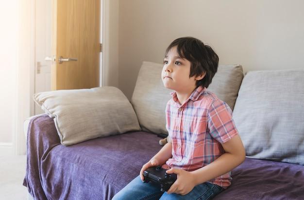 Porträt des kindes, das videospiel oder spielekonsole hält. kind, das spiel online zu hause spielt, während schule weg ist, junge bleibt zu hause
