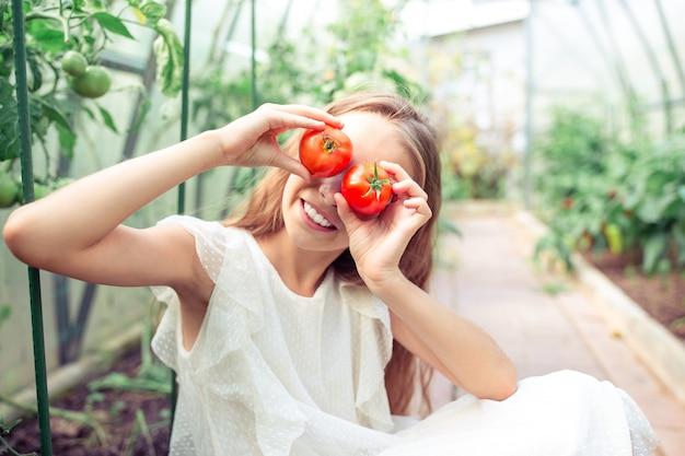 Porträt des kindes mit der großen tomate in den händen im gewächshaus