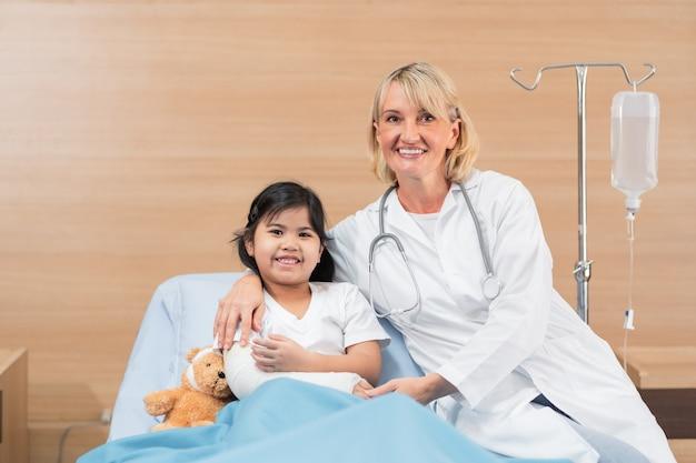 Porträt des kleinen arztkinderarztes und des kleinen mädchenpatienten auf bett mit teddybär