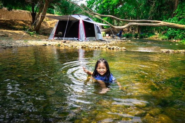 Porträt des kleinen asiatischen mädchens, das naturwasser nahe zelt spielt, während camping im naturpark geht
