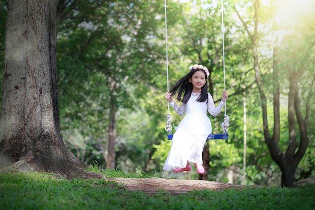 Porträt des kleinen asiatischen mädchens, welches das schwingen unter dem großen baum im naturwald spielt
