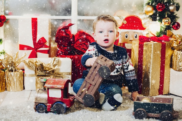 Porträt des kleinen blonden jungen, der auf dem boden im dekorierten studio sitzt und mit weihnachtsgeschenken und -schachteln spielt