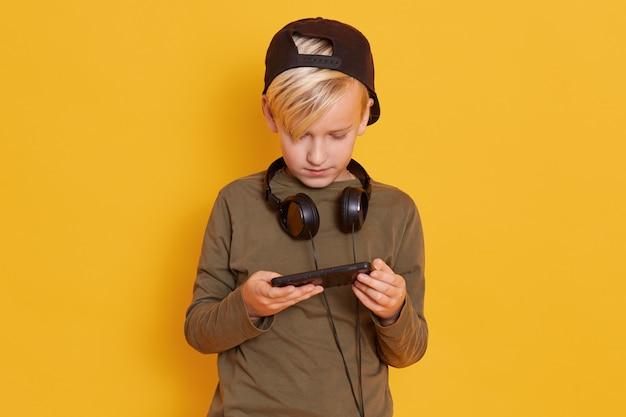Porträt des kleinen blonden kindes, das videospiel spielt und smartphone in händen hält