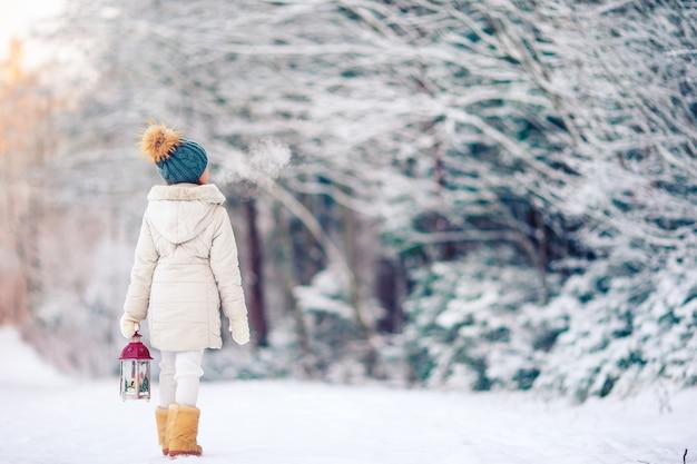 Porträt des kleinen entzückenden mädchens am sonnigen wintertag des schnees