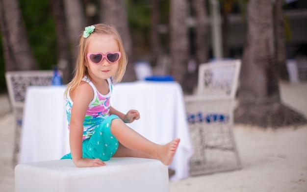 Porträt des kleinen entzückenden mädchens auf einem tropischen weißen strand