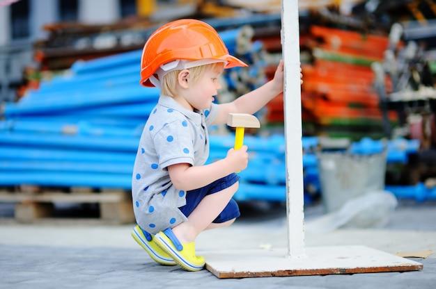 Porträt des kleinen erbauers in den hardhats mit dem hammer, der draußen arbeitet