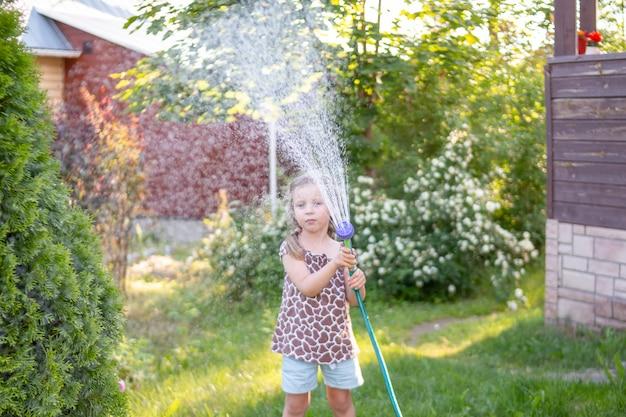 Porträt des kleinen gärtnermädchens, sie gießt blumen auf dem rasen nahe häuschen.
