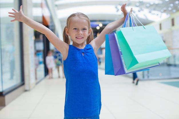 Porträt des kleinen glücklichen mädchens, das im einkaufszentrum einkaufstaschen hält